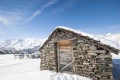 在雪的被隔绝的山小屋 库存照片