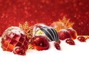 在雪的许多圣诞节球在红色背景 免版税库存照片