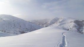 在雪的足迹在山 库存图片