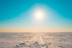 在雪的路在明亮的太阳发光的绿松石天空的冬天多雪的沙漠 库存图片