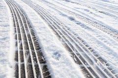 在雪的车胎轨道在街道上 库存图片