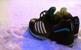 在雪的运动鞋 图库摄影