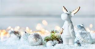 在雪的逗人喜爱的矮小的白色圣诞节驯鹿 库存图片