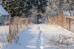 在雪的道路在两个庭院之间 免版税图库摄影