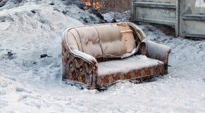在雪的长沙发 免版税库存照片