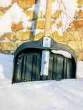 在雪的雪铁锹在砖墙的背景 免版税库存图片