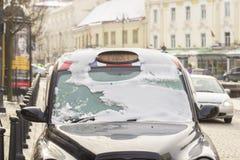 在雪的黑城市出租车 库存照片