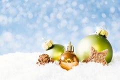 在雪的绿色和金黄圣诞节球 免版税库存图片