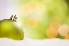 在雪的绿色圣诞节装饰品在抽象背景 免版税库存照片