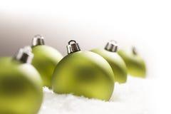 在雪的绿色圣诞节装饰品在灰色背景 免版税库存图片
