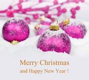 在雪的紫色圣诞节装饰 免版税库存图片