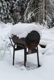 在雪盖的一个老bbq格栅 免版税库存图片