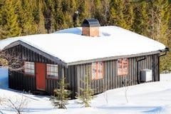 在雪盖的一间典型的黑挪威客舱的侧视图 免版税库存照片