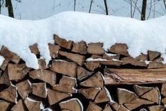 在雪盖的切好的木头 库存图片