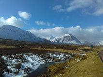 在雪盖的格伦克立场山在冷漠的天空蔚蓝下当雪融解入Rannoch的河停泊 免版税图库摄影