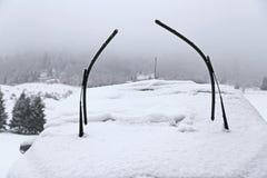 在雪盖的汽车风档刮水器在飞雪以后 库存照片