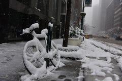 在雪盖的自行车在冬天风暴Niko曼哈顿,纽约期间 库存照片