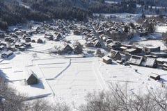 在雪盖的茅屋顶房子 免版税库存图片