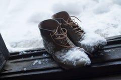 在雪盖的葡萄酒皮鞋由门 库存照片