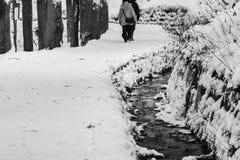 在雪盖的长的远足的道路用跑在边下的小小河 免版税库存图片