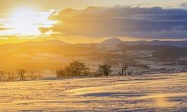 在雪盖的风景小山的冬天日落 库存图片