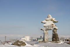 在雪盖的Inukshuk或Inuksuk地标在Rankin入口,努纳武特的社区的小山发现了 库存图片