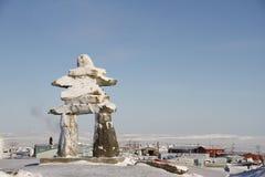 在雪盖的Inukshuk或Inuksuk地标在Rankin入口,努纳武特的社区的小山发现了 免版税库存照片