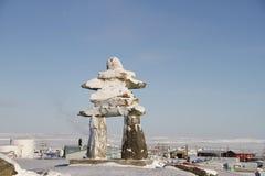 在雪盖的Inukshuk或Inuksuk地标在Rankin入口,努纳武特的社区的小山发现了 免版税图库摄影