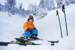 在雪穿戴滑雪成套装备的一点滑雪者男孩休息 免版税库存照片