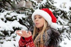 在雪结构树附近的美丽的圣诞节女孩 免版税库存照片