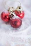 在雪背景的发光的红色圣诞节球 免版税库存照片