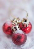 在雪背景的发光的红色圣诞节球 库存照片