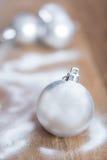 在雪背景的发光的银色圣诞节球 图库摄影