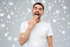 在雪背景的打呵欠的人 图库摄影