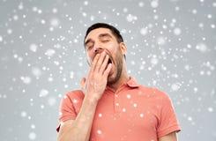在雪背景的疲乏的打呵欠的人 免版税库存照片