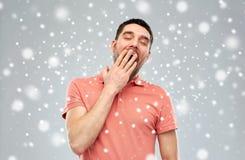 在雪背景的疲乏的打呵欠的人 图库摄影