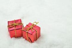 在雪背景的红色小包 库存图片