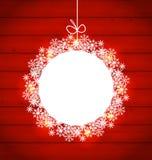 在雪花做的圣诞节圆的框架在红色木backgroun 库存照片