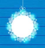 在雪花做的圣诞节圆的框架在蓝色木backgrou 库存图片