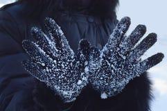 在雪花特写镜头的黑手套 免版税库存照片