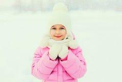 在雪花的冬天画象愉快的微笑的小女孩孩子 库存图片