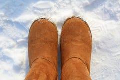在雪解雇冬天温暖的ugg起动 免版税库存照片