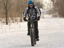 在雪足迹的肥胖自行车 库存图片