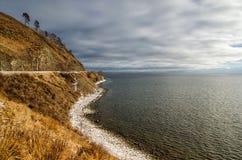 在雪风暴以后的湖与多云天空和棕色山 Baikal湖,西伯利亚,俄罗斯 库存图片