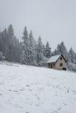 在雪风暴中间的被放弃的房子 库存照片
