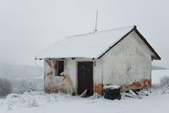 在雪风暴中间的被放弃的房子 免版税库存图片