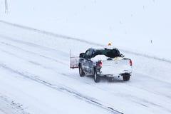在雪风暴以后犁在高速公路的卡车2013年 图库摄影