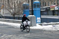 在雪风暴期间,人做在自行车的交付 库存图片