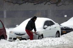 在雪风暴期间,人挖掘有铁锹的汽车 免版税库存图片