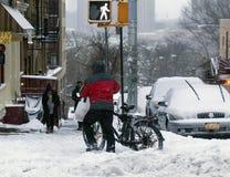 在雪风暴期间,人推挤自行车 图库摄影